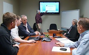 Group of men meeting in a conference room and referencing a TV screen on the wall.