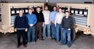 Group of white males standing in front of Mandus Group resupply units in desert tan metal.