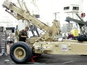 Side view of a desert tan-colored M198 howitzer being inspected