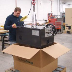 Man placing a Mandus unit inside of a cardboard box in preparation for shipping.