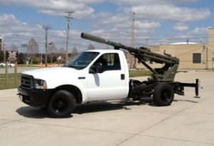 Hawkeye Artillery Cannon mounted on top of a white Ford truck.