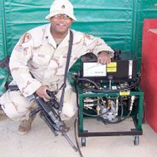 Soldier in desert fatigues crouching next to a Mandus Group Oil Transfer System.